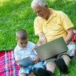 Grandfather and child using laptop and tablet computer — Stock Photo #65953685