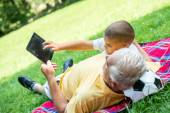 Grandfather and child in park using tablet — Stock Photo