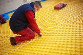 Worker installing underfloor heating system — Stock Photo