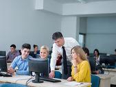 Студенты с учителем в классе лаборатории компьютера — Стоковое фото