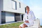 Senior man in front of modern home — Stock Photo