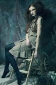 Fashion model sitting on a stool — Stockfoto
