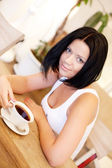 Young woman sitting in a cafe drinking coffee — Stock Photo