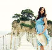 Young woman with summer hat posing on the bridge — Stock Photo