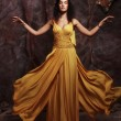 Brunette woman wearing yellow evening dress — Stock Photo #65889133