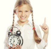 Little girl with a silvered alarm-clock — Stock Photo