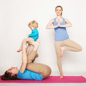 Mother, father and son doing yoga — Stock Photo