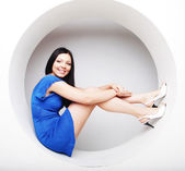 Brunette in blue dress sitting in a circle — Stock Photo
