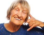 Senior happy woman is making a call me gesture — Stock Photo
