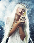 Angelic long hair woman with skull — Stock Photo