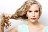 Woman holding her long curly healthy hair — Stock Photo