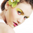 Beautiful stylish girl with orchid flower in hair. — Stock Photo #69685739