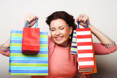 Beautiful young woman with colored shopping bags — Stock Photo