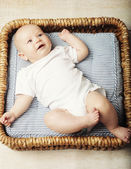 Little cute baby lying in basket — Stock Photo