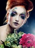Beautiful redhair woman  holding flowers — Photo