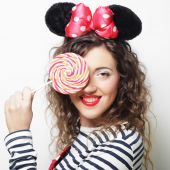 Young curly woman with mouse ears holding lollipop — Stockfoto