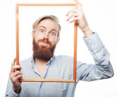 Young man holding picture frame — Stock Photo