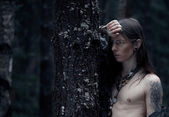 Young man with long hair in the dark forest — Stock Photo