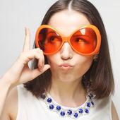 Young happy woman with big orange sunglasses — Stock Photo