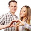 Happy couple  showing heart with their fingers — Stock Photo #72326259