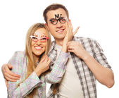Lovely couple holding party glasses on stick — Stock Photo