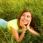 Young beautiful girl lays on a grass — Stock Photo