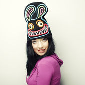 Playful young woman in funny hat with rabbit — Stock Photo