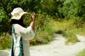Young woman photographer taking photo, summer day — Stock Photo