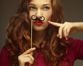 Girl wearing fake mustaches.  — Stock Photo