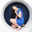 Brunette in blue dress sitting in a circle — Stock Photo #73786183