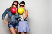 Hipster girls smiling and holding colored balloons — Stock Photo