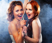 Beauty girls with a microphone singing and dancing — Stock Photo