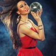 Young  woman in red dress keeping disco ball — Stok fotoğraf #79305200