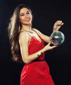 Young  woman in red dress keeping disco ball — Stock Photo