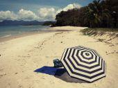 Striped umbrella on a beach — Stockfoto