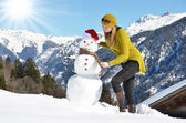 Girl decorating a snowman — Stock Photo