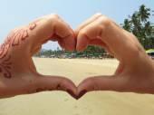 Palolem beach skrze ruce ve tvaru srdce. — Stock fotografie