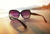 Sunglasses on  sand of Palolem beach. — Stock Photo