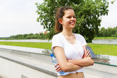 Young girl resting by river. Joging outfit. — Stock Photo