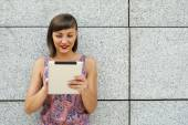 Young modern woman using tablet in the city by the wall, smiling — Stock Photo