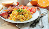 Scrambled eggs with bacon — Stock Photo