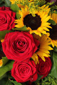 Red roses and sunflowers in a floral arrangement — Stock Photo