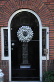 Silver christmas wreath with decorations on a door — Stock Photo
