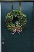 Classic christmas wreath with decorations on a door — Stock Photo