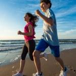 Teenage girl and boy running on beach — Stock Photo #75238249