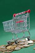Coins under shopping basket — Stock Photo