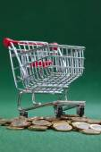 Coins under shopping basket — Foto Stock