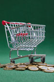 Coins under shopping basket — Стоковое фото