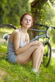 Mulher sentada perto de bicicleta — Foto Stock