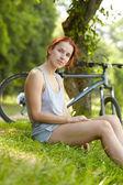 Woman sitting near bike — Stock Photo